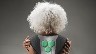 Photo of the back of an elderly person with wavy white hair. She is seen wearing a soft exoskeleton and holding both her arms.