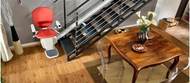 Photo d'une pièce avec une table à manger avec des chaises au milieu. Dans le coin se trouvent des escaliers et un monte-escalier y est attaché.