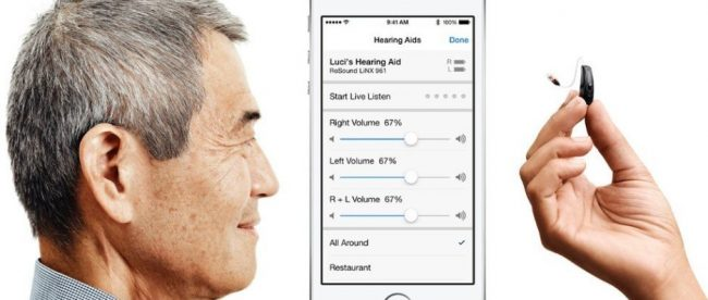 Photo shows the side profile of a man to the left, an IPhone in the middle, and a hand holding a cochlear implant). The screen on the iPhone shows volume settings for hearing aids.