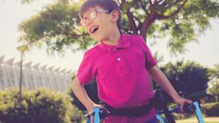 A child wearing a megenta shirt and glasses seen holding a walker. He is smiling.