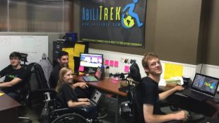 Abilitrek team members in their office. They are looking at the camera and smiling.