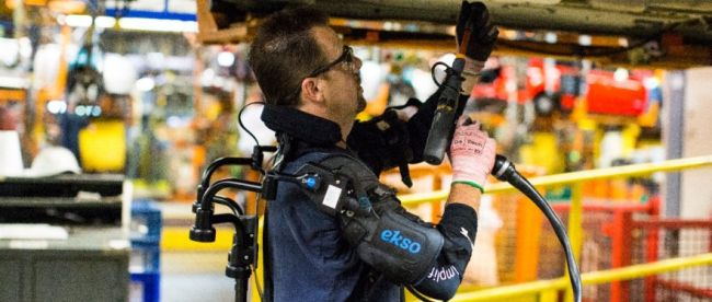 a person seen working on a car in an assembly line in a car manufacturing plant. This person is wearing the eksovest, and is seen drilling into the car body that is in an overhead position.