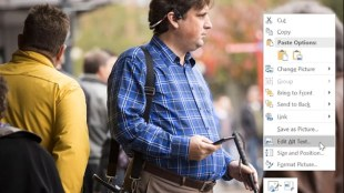 "A photo displayed on a computer of a man wearing bone conducting headsets, and holding a phone in his right hand and a cane in his left. To the right is the context menu (right click menu) from an office product, and the option ""edit alt text"" is highlighted"""