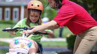 9 year old bella cates is seen on her bike. One of the students who designed the bike is seen adjusting her bike's handle bars.