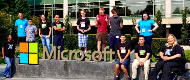 students posing for a photo. They are all seen standing around a physical microsoft logo at the microsoft campus.