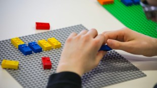 close up of a child's hands shown playing with braille lego blocks. Braille legos will have letters, numbers and punctuation printed on them as well so both sighted and blind children can play together.