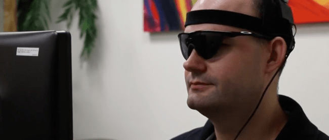 a person with acquired blindness is seen wearing sunglasses with camera attached to them. He is sitting in front of a computer.