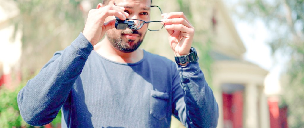 A man seen putting on glasses that have TranscribeGlass attached to them.
