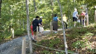 A group of people seen hiking on a Braille trail. They are holding a rope that guides them on the trail.