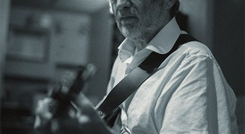 black and white photo of Trevor Owen playing the guitar