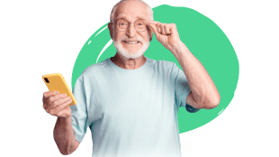 an elderly man seen smiling and holding a cell phone with yellow cover in his right hand adjusting his glasses with his left.