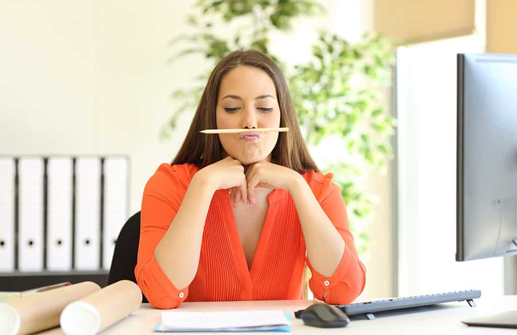 Woman looks bored at work - has a pencil under her nose and is wasting time instead of working