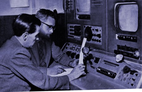 """Lou Rivers, presentation manager, checks a """"running order"""" with Stuart Harris, senior telecine engineer in the Telecine Room."""
