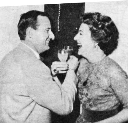 """Noele Gordon and Jerry Allen link arms for a """"Happy Christmas and Happy Birthday"""" toast"""