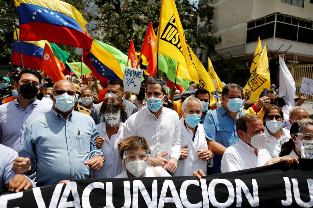 Venezuela's opposition leader Juan Guaido (C) walks with healthcare workers and fellow opposition politicians during a protest to demand that all people get vaccinated against the coronavirus disease (COVID-19), in Caracas, Venezuela April 17, 2021. REUTERS/Leonardo Fernandez Viloria/File Photo