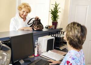 Consistent Dental Hygiene Schedules Require The Dental Front Office To Gather Solid Contact Information From Their Patient. An elderly female patient stands at the dental front desk talking with the dental front office team member.
