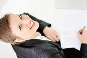 A dental office administrator signing a dental financial agreement.