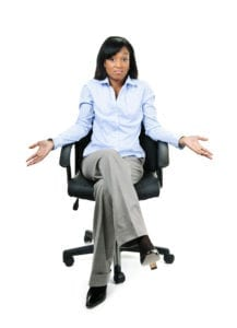 A dental administrative professional sits in a chair and holds her hands out asking what are you waiting for?