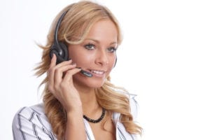 A dental front office team member wears a headset to answer the phone. Training new dental front office team members is essential for dental practice success.