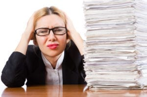 A huge stack of white papers next to a woman holding her head. She has tremendous dental front desk stress.