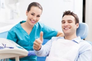 The Dental Hygiene Schedule Master Class Teaches How To Create & Maintain The Ideal Dental Hygiene Schedule. A dental hygienist sits with a male dental patient in the dental office.