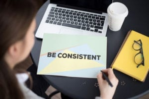 """It is important that the dental office is consistent in managing their hygiene reactivation systems. A woman sits at her computer with a note in front of her that says """" Be consistent"""" Dental office hygiene reactivation requires consistency."""