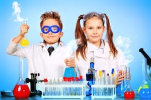 A young boy and girl stand in front of a science experiment. There is a science behind learning dental hygiene scheduling.