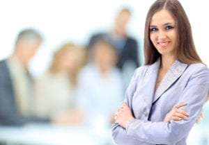 A female professional stands in front of a group of other professionals who are faded out in the background. Learning dental restorative scheduling takes time, education, and experience.