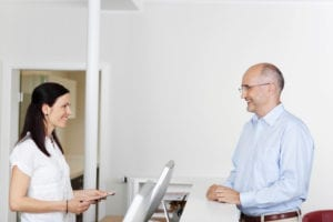 Great schedule management is a piece of building trust with dental patients. A dental front office team member is scheduling a dental patient at the dental front office.