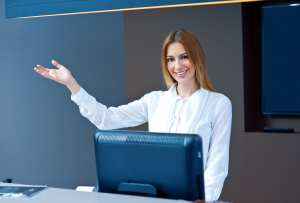 A dental front office team member smiles and holds her hand up in a friendly manner.