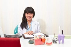 A dentist smiles as she sits at her desk. Her dental front office is organized and taking good care of the practice with the support of a checklist.