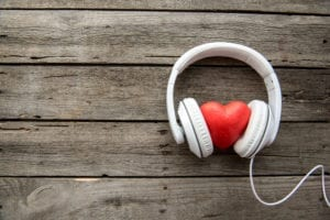 Headphones hold a heart to represent listening to dental patient complaints.
