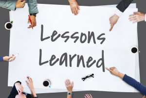 """A team of hands hold a large piece of paper that says """"Lessons Learned"""" It represents the dental team learning from patient complaints."""