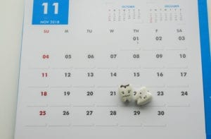 A tooth rests on a calendar representing that it is time for a hygiene visit to the dentist.