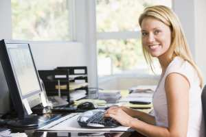 A dental front office team member works at her computer on dental claims over 30 days.