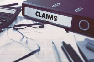 A binder holds claims that sit on a desk. This represents dental claims over 30 days that must be called on.