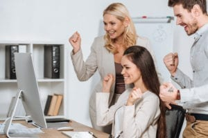 A young woman celebrates with 2 coworkers that she is learning her front desk skills on the job.