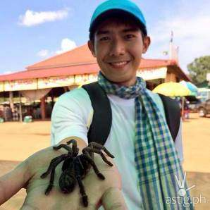 Robi Domingo showing off a tarantula in Cambodia