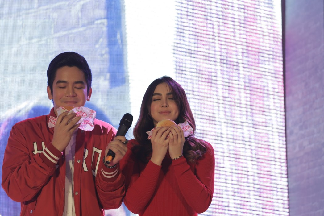 """Langhap"" then ""Sarap"" Joshua Garcia and Julia Baretto demonstrate the two-step process of enjoying the Jollibee Yum Burger"