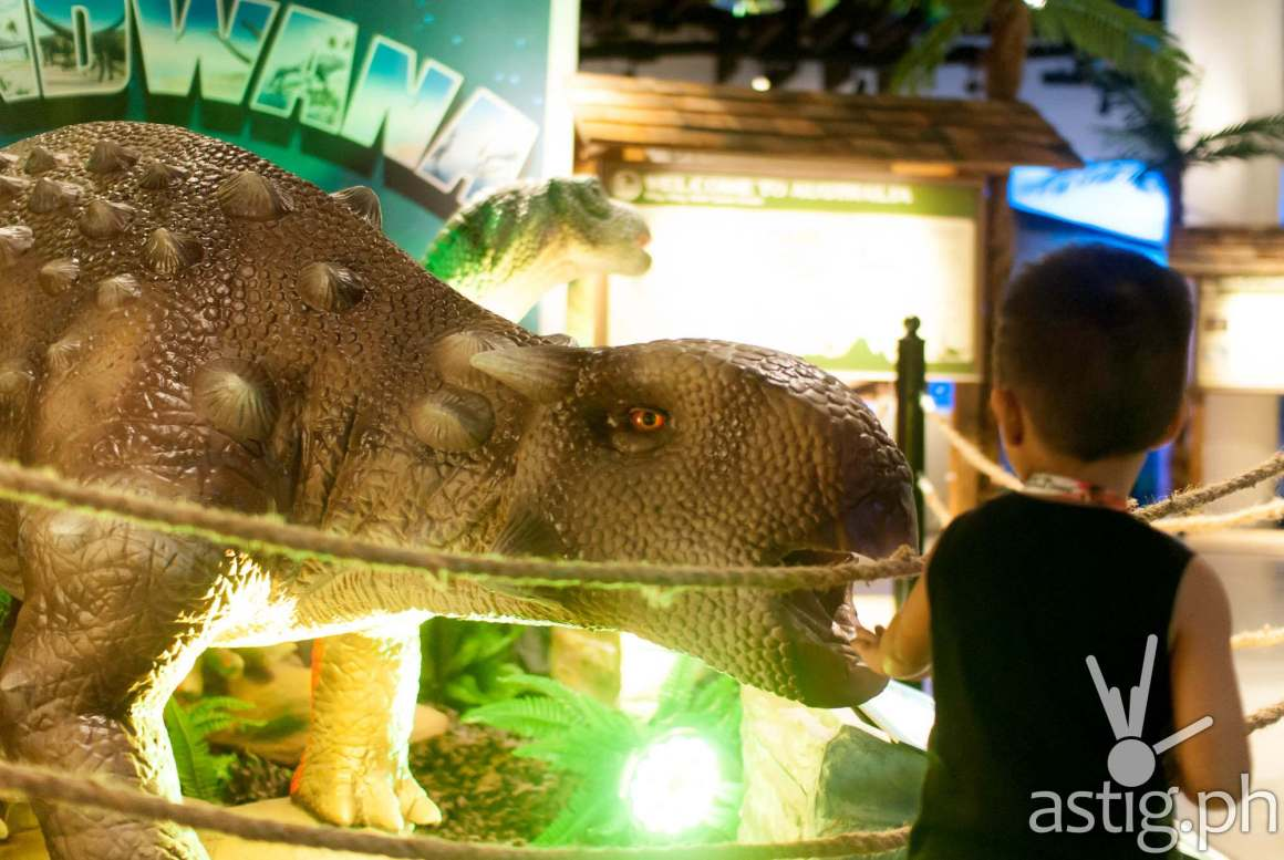 Kid touching animatronic dinosaur -Dinosaurs Around The World exhibit - Mind Museum BGC