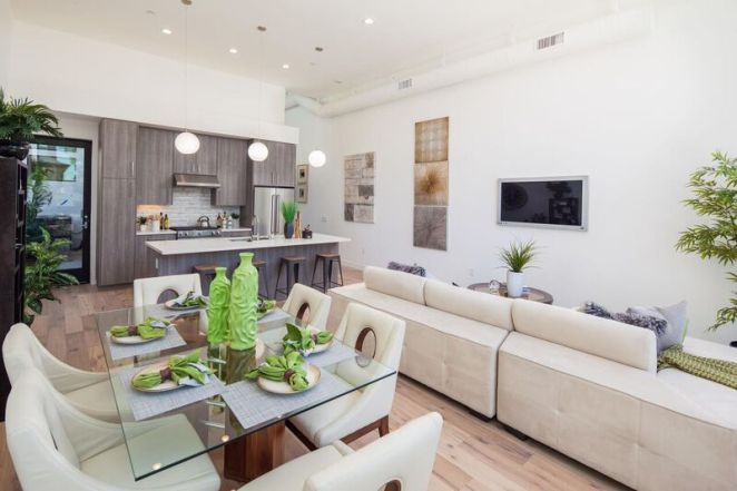 Kitchen, dining room and living room staging with beige and green accents
