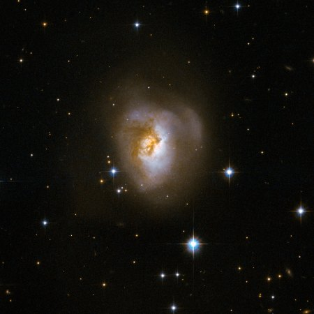 """MCG+08-11-002 is an odd-looking galaxy with a spectacular dark band of absorbing dust in front of the galaxy's centre, making it resemble a """"Black Eye"""". Scientists believe that it is the remnant of an earlier collision of two separate galaxies. This peculiar galaxy is at the centre of a rich field of foreground stars, close to the plane of our own Milky Way galaxy. MCG+08-11-002 is about 250 million light-years away in the constellation of Auriga, the Charioteer. This image is part of a large collection of 59 images of merging galaxies taken by the Hubble Space Telescope and released on the occasion of its 18th anniversary on 24th April 2008."""