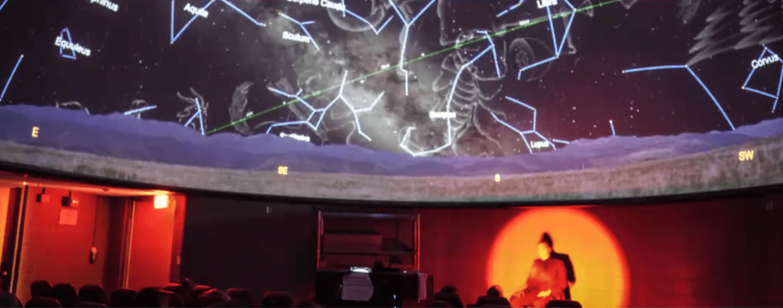 A planetarium show accessible to deaf audiences, with a red light illuminating the ASL interpreter.