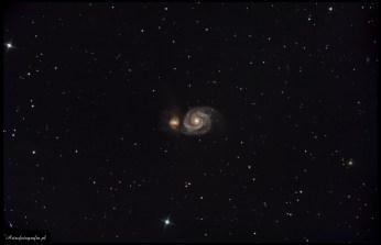 """Teleskop SkyWatcher Newton 8"""" (200/1000), zmodyfikowany 300D - 11x420s, montaż Takahashi EM200. M51 to jeden z tych """"nieśmiertelnych"""" obiektów, do, których wraca się bardzo często. Sama para galaktyk jest dość jasna, ale niestety ma niewielkie rozmiary kątowe, przez co w pełnej krasie można ją podziwiać dopiero fotografując używając długiej ogniskowej. Ponieważ pogoda od połowy 2007 roku jest mało łaskawa, postanowiłem wykorzystać wieczór, w którym można było fotografować przez zaledwie dwie godziny (później wschodził Księżyc) a to niestety jest zdecydowanie zbyt mało, na pokazanie ciemnych ramion pyłowych otaczających tą parę galaktyk. Niestety okazało się, że seeing tego wieczora jest niezwykle słaby, przez co ostrość zdjęcia spadła w znacznym stopniu."""