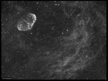 Teleskop Celestron 80ED + TV 0,8x (480mm), SBIG ST2000XM - 18x900s Ha 6nm, montaż Takahashi EM200. Mgławica Półksiężyc można by powiedzieć, że znajduje się w samym sercu gwiazdozbioru Łabędzia. To piękny i jasny obiekt. Jego strukturę ukazuje dopiero dłuższa ogniskowa i długotrwałe naświetlanie. Pole które zastosowałem w tym zdjęciu pokazuje bogate otoczenie wokół tej mgławicy. Pofalowane wodorowe struktury przypominają refleksy światła we wodzie, a mgławica wygląda jak wielka płaszczka płynąca pośród nich.