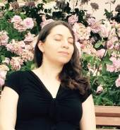About Astro Healer: Author and Astrologer Tina meditating against a background of pink flowers.