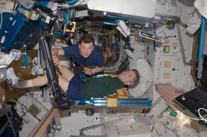 ISS-20_Robert_Thirsk_exercises_using_the_aRED_in_the_Unity_node_Roman_Romanenko_assists