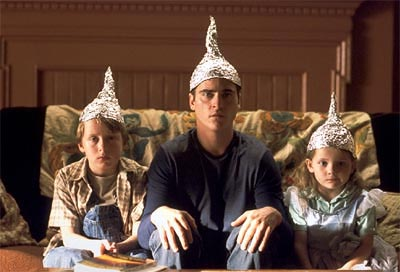 İşaretler filminden bir kare: üç kardeş alüminyumdan yaptıkları başlıklarla tv seyrediyor.