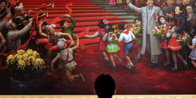رجل ينظر إلى لوحة لماو في قاعة الشعب الكبرى في بكين