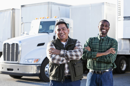 Hispanic and African American truck drivers standing in front of semi-trucks.